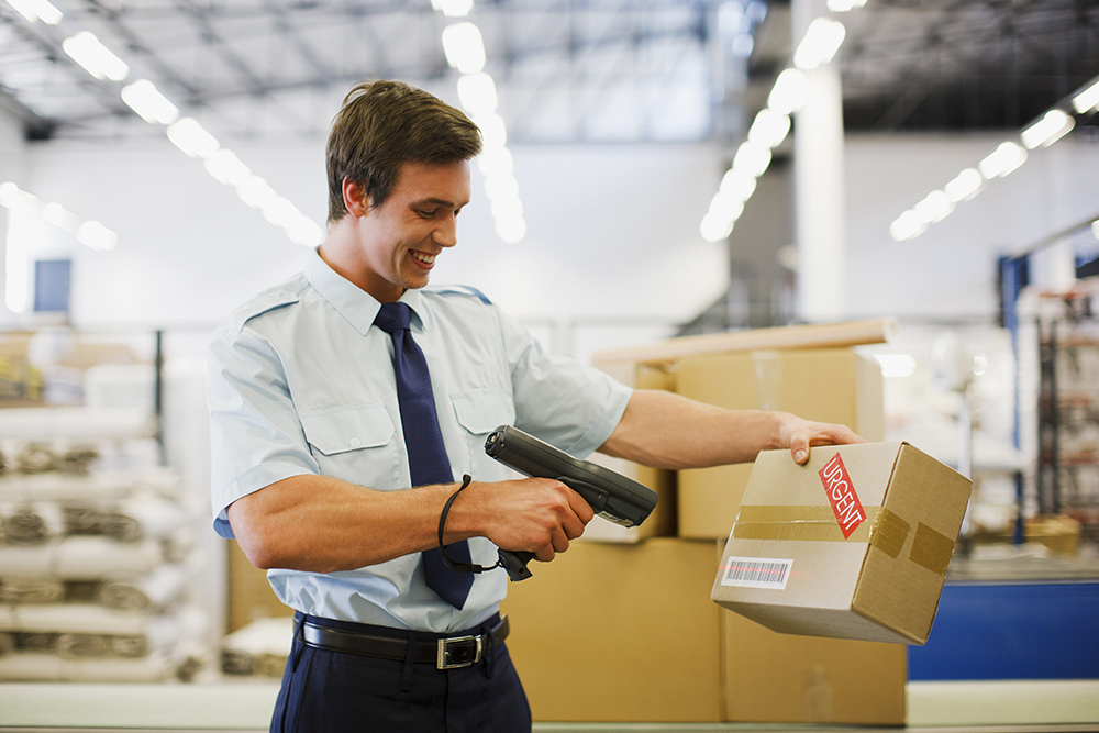 Employee smiling and scanning a package in a warehouse